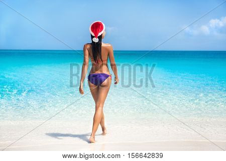 Bikini woman in santa hat on tropical beach for Christmas vacation travel.