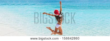 Christmas fun beach banner panorama blue ocean water background. Christmas vacation paradise holiday. Bikini woman jumping of joy and success enjoying caribbean sun travel getaway with santa hat.
