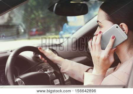 Woman with cellphone driving a car