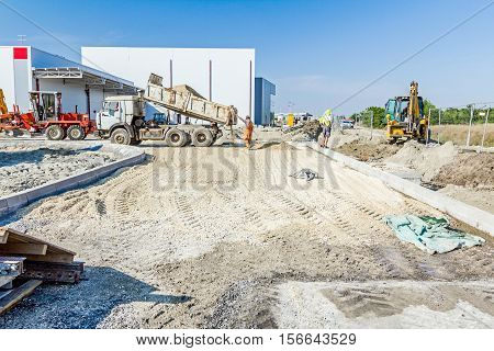 Dumper truck is unloading soil or sand at construction site. Landscape transform into urban area.