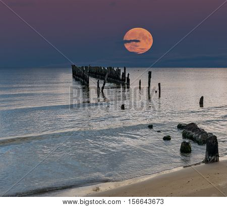 Rise of  Super moon, Baltic Sea, remains of old fishery pier