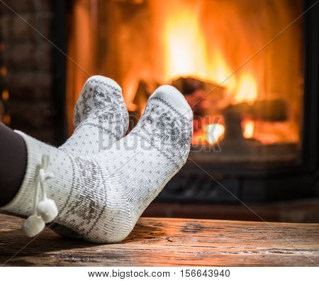 Warming and relaxing near fireplace. Woman feet near in front of fire.