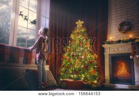 Merry Christmas and happy holidays! Cute little child girl looking by window. Christmas miracle Santa Claus flying in his sleigh against moon sky. Room decorated on Christmas. Kid enjoy the holiday.