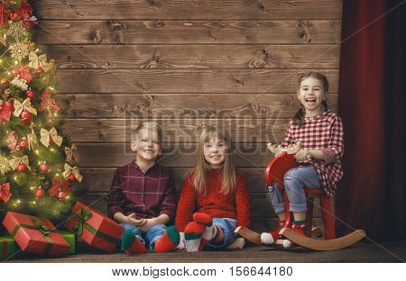 Merry Christmas and Happy Holidays concept. Group of three children on wooden background. Portrait of beautiful cute little kids against decorated tree.