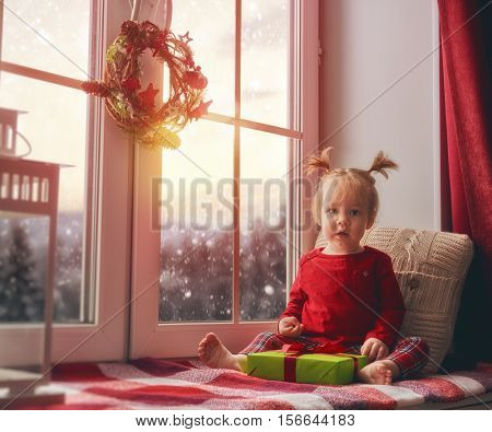 Merry Christmas and happy holidays! Cute little baby girl sitting by the window and looking at the winter forest. Room decorated on Christmas. Kid holding present gift box.