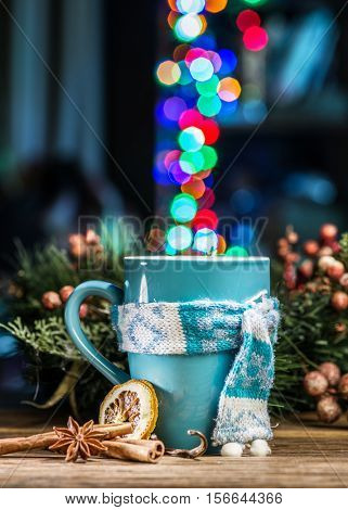 Cup with magic colorful lights and spices. Christmas background.