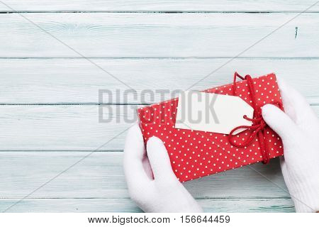Hands holding christmas or valentines day gift above wooden table. Top view with copy space
