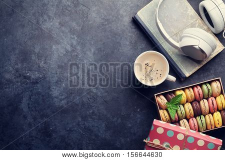 Colorful macaroons in a gift box and headphones on stone table. Sweet macarons. Top view with copy space for your text. Toned