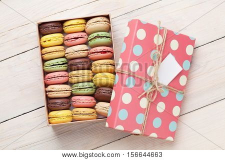 Colorful macaroons on wooden table. Sweet macarons in gift box. Top view