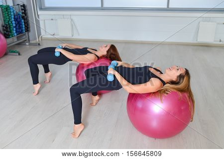 Fitness, sport, exercising lifestyle - Group of women doing exercises with dumbbells and fit ballsin a Pilates class at the gym.
