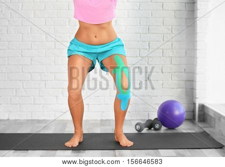 Woman with elastic bandage on knee doing sport exercises in gym