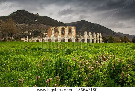 View of Gubbio in the spring with flowers and dark clouds