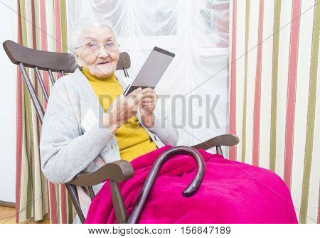 Elderly lady sitting in a nursing home and reading.