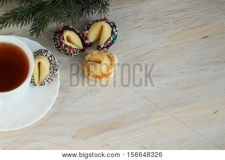 four decorated fortune cookies and a cup pf tea on wooden background