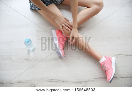 Woman wearing pink sneakers on wooden floor background