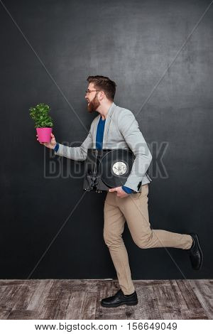 Guy with vynil and flower. in profile. full length portrait