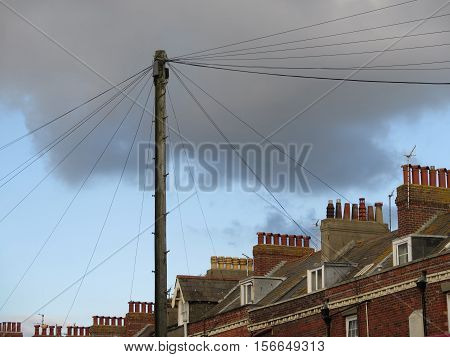 Telegraph Pole and Chimney Stacks against cloudy sky in Weymouth Dorset UK