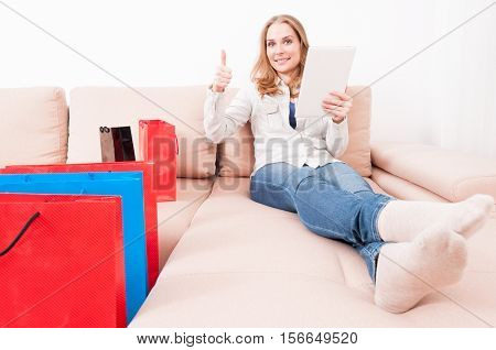 Woman Laying On Chouch With Tablet Showing Like