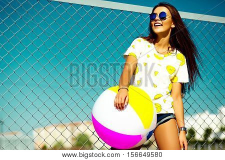 Funny crazy glamor stylish sexy smiling beautiful young woman model in bright hipster summer casual cloth with colorful ball in the street behind blue sky
