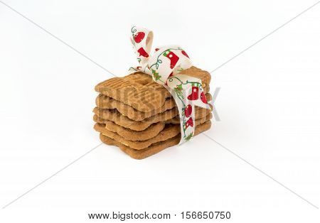 Stacked Spiced Biscuits with Almonds ( Spekulatius ) decorated with festive Christmas Bow on white background.