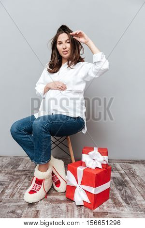 Photo of pregnant woman with gifts. full lenght. looking at camera