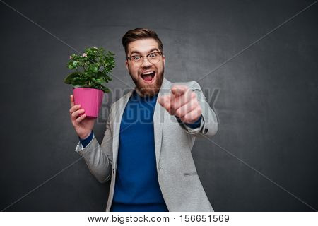 Man with flower pointing his fingers on camera. in studio. looking at camera. isolated black background