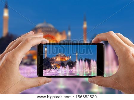 Travel concept. Hands making photo of night city with smartphone camera. Istanbul at sunset. Turkey.