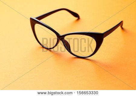 Brown glasses on orange background