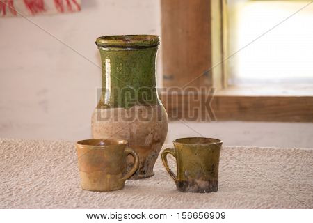 Clay jug and cups on the table