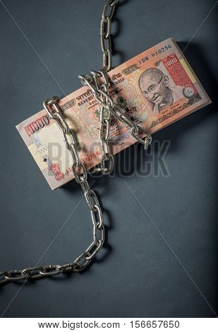 A stack of banned one thousand rupee Indian currency notes wrapped with steel chain. A concept.
