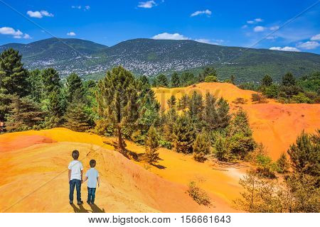 Two boys - brothers of seven and four years admire the magnificent nature. Orange and red picturesque hills in Languedoc - Roussillon, Provence