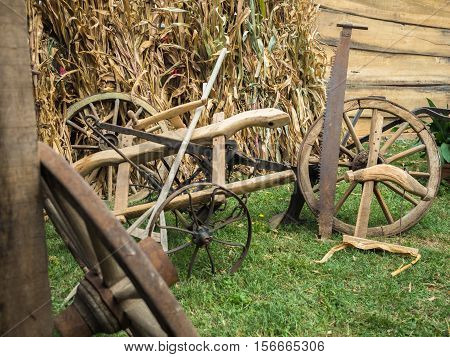 Picture of the old cart-wheels at the farm. Wooden and iron cart-wheels with saw on green grass. Agricultural implement before wooden fence and haulm.