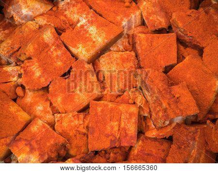 Background of the pieces of smoked lard. Orange smoked lard pattern close up
