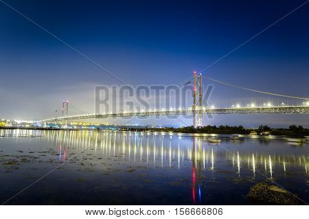 Reflection Of A Bridge In The Sea At Night