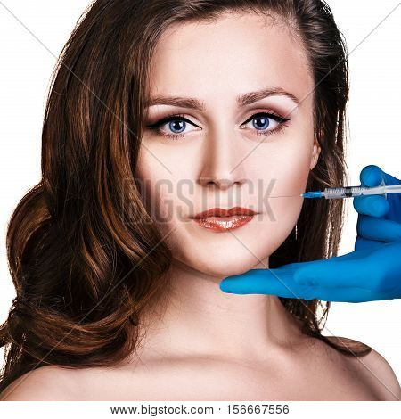 Woman make an injection from a syringe over white background. Beauty procedure concept.
