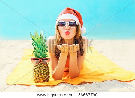 Christmas Portrait Pretty Young Woman In Red Santa Hat With Pineapple Sends Air Kiss Lying On Beach