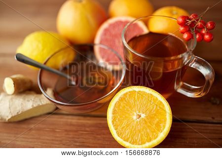 health, traditional medicine, folk remedy and ethnoscience concept - cup of ginger tea with honey, orange and rowanberry on wood