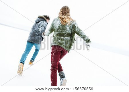 young couple running across the frozen lake