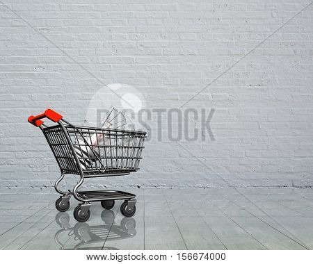 Shopping cart with large light bulb side view on brick wall and wooden floor background.