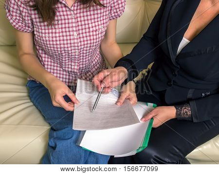 The insurance agent makes a deal sign documents. The tablet in female hands. A woman touching the screen with her finger.