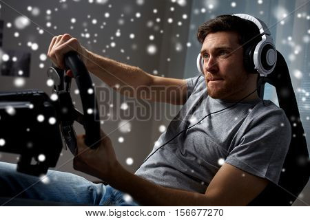 technology, gaming, entertainment and people concept - young man in headphones with pc computer playing car racing video game at home and steering wheel over snow