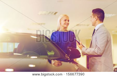 auto business, car sale, consumerism and people concept - happy woman with dealer talking in auto show or salon