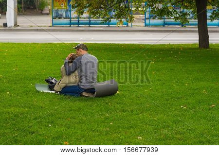DNEPR UKRAINE - SEPTEMBER 25 2016:Young loving couple sitting on a ground pad on green lawn on Dnepr river embankment in center of Dnepr city, Ukraine at September 25, 2016