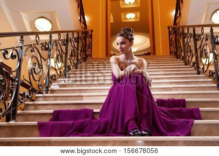 woman in a long dress is sitting on the stairs in the hotel lobby