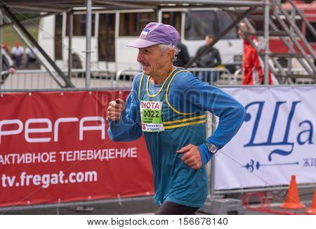 DNEPR, UKRAINE - SEPTEMBER 25, 2016:Portrait of senior participant hurrying to finish line during