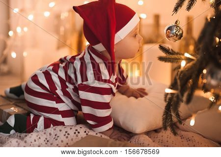 Baby girl 1 year old crawling under Christmas tree wearing body suit in red and white color. Looking at Christmas ball. Holiday season.