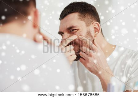 beauty, skin problem, winter, christmas and people concept - young man looking to mirror and squeezing pimple at home bathroom over snow