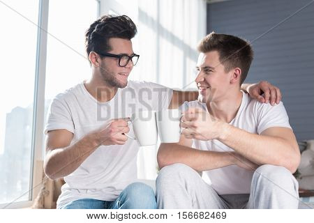 alternative relationships. Joyful young homosexual couple smiling and having a hot drink together while relaxing in an airy room.