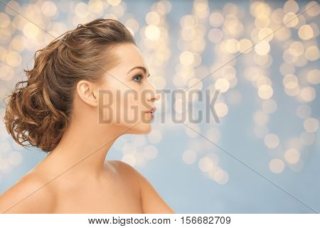health, people, plastic surgery, holidays and beauty concept - beautiful young woman face over lights background
