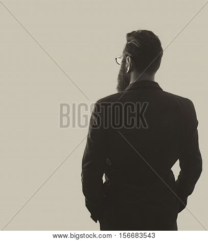 Silhouette of a man in a business suit. The man with glasses and beard looks ahead. There is space for your text. Isolated on white.